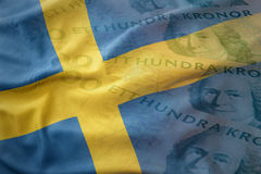 Colorful waving national flag of sweden on a swedish crown money banknotes background. Finance concept Stock Images