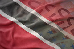 Colorful waving national flag of trinidad and tobago on a euro money banknotes background. Royalty Free Stock Images