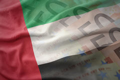 Colorful waving national flag of united arab emirates on a euro money banknotes background. Royalty Free Stock Images