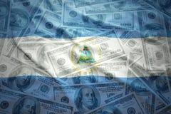 Colorful waving nicaraguan flag on a dollar money background. Colorful waving nicaraguan flag on a american dollar money background Royalty Free Stock Photography