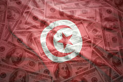 Colorful waving tunisian flag on a dollar money background. Colorful waving tunisian flag on a american dollar money background royalty free stock images