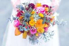 Bride bouquet in the hand of a woman. Colorful wedding bouquet, daffodils, gerbera, roses in bride hand with lacy white wedding dress detail stock photos
