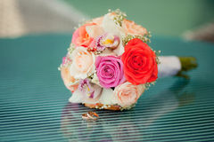 Colorful wedding bouquet with orchid and. Pastel wedding bouquet with roses on blue glass table Stock Image