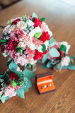 Colorful wedding bouquet with roses and carnations on the table next to bridesmaids Boutonniere and box with rings Royalty Free Stock Images