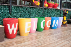 Colorful welcome perspective view. Bright and colorful letter on the pots say welcome Royalty Free Stock Photos