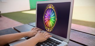 Composite image of colorful wheel of fortune on mobile screen. Colorful wheel of fortune on mobile screen against close up of boy using digital laptop while Stock Photos