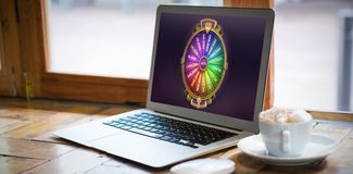 Composite image of colorful wheel of fortune on mobile screen. Colorful wheel of fortune on mobile screen against laptop by coffee cup on table in cafe Royalty Free Stock Image