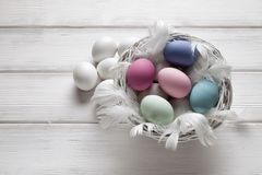 Colorful and white easter eggs in basket Royalty Free Stock Image