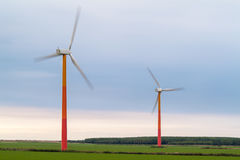 Colorful wind turbines on a green meadow Royalty Free Stock Photo