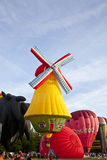 Colorful windmill and red air balloons taking off Royalty Free Stock Photos
