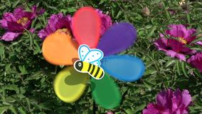 Colorful windmill toy with bee picture near peony bush, slow motion stock video