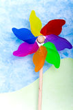 Colorful windmill toy on green hills Royalty Free Stock Images