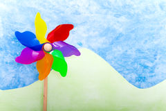 Colorful windmill toy on green hills Royalty Free Stock Photography