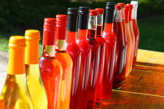 Colorful Wine Bottles in a Row on a Wooden Table in the Sun Stock Images