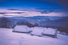 Colorful winter sunrise in the mountains. Fantastic morning glowing by sunlight. View of the snowy forest and old wooden hut cabin Stock Image