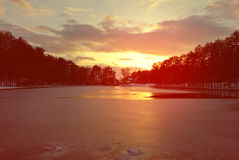 Colorful winter sunset above a frozen mountain lake. Beautiful colorful winter sunset above frozen mountain lake, with dramatic red sky. Image filtered in faded Royalty Free Stock Photography