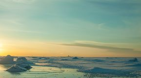 Colorful winter sunset over cracked ice. Deserted surface of frozen sea covered by snow and blue sky with cirrus clouds. stock photo