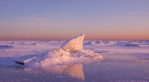 Colorful winter sunset over the cracked pink ice with reflection. stock photography