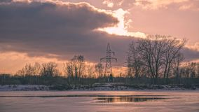 Colorful winter sunset with trees and power lines in background. And ice blocks - vintage retro effect Stock Photography