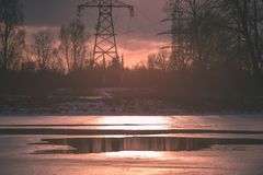 Colorful winter sunset with trees and power lines in background. And ice blocks - vintage retro effect Stock Photo