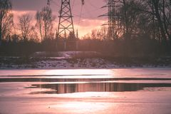 Colorful winter sunset with trees and power lines in background. And ice blocks - vintage retro effect Stock Photos