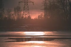 Colorful winter sunset with trees and power lines in background. And ice blocks - vintage retro effect Stock Image