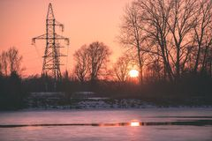 Colorful winter sunset with trees and power lines in background. And ice blocks - vintage retro effect Royalty Free Stock Photo