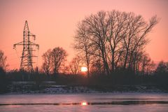 Colorful winter sunset with trees and power lines in background. And ice blocks - vintage retro effect Royalty Free Stock Photography