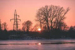Colorful winter sunset with trees and power lines in background. And ice blocks - vintage retro effect Stock Images