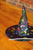 A colorful witches hat. Displayed with a stick used as a wand Stock Image