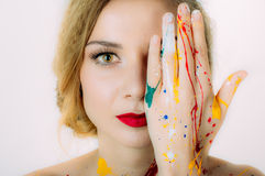Colorful woman portrait in paint with hand near the eyes Royalty Free Stock Images