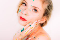 Colorful woman portrait in paint with hand near the face Royalty Free Stock Photography