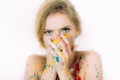Colorful woman portrait in paint  with hands closing mouth Royalty Free Stock Photos