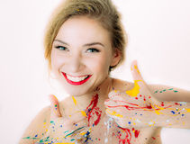 Colorful woman portrait in paint with red lips making thumbs up Stock Images