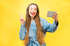 Colorful woman portrait. Young and smiling woman in the blue coat making self portrait with smart phone standing on the yellow wall background Stock Images