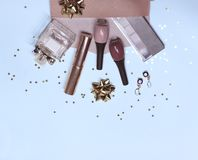 Colorful cosmetic set on blue background with stars and gift bow, flat stock photos