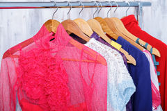 Colorful womens clothes on hangers on rack in fashion store. wom. Colorful womens clothes on wood hangers on rack in a fashion store. women`s closet royalty free stock image