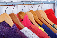 Colorful womens clothes on hangers on rack in fashion store. wom. Colorful womens clothes on wood hangers on rack in a fashion store. women`s closet stock photography