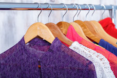Colorful womens clothes on hangers on rack in fashion store. wom. Colorful womens clothes on wood hangers on rack in a fashion store. women`s closet stock image