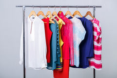 Colorful womens clothes on hangers on rack on gray background. w. Colorful womens clothes on wood hangers on rack on gray background. women`s closet royalty free stock image
