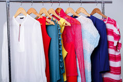 Colorful womens clothes on hangers on rack on gray background. w. Colorful womens clothes on wood hangers on rack on gray background. women`s closet stock images
