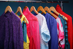Colorful womens clothes on wood hangers on rack on blue backgrou. Nd. women`s closet closeup royalty free stock photos