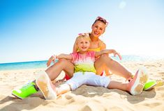 Happy modern mother and daughter sitting on seacoast. Colorful and wonderfully cheerful mood. happy modern mother and daughter in colorful clothes sitting on the royalty free stock photos