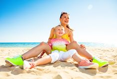 Happy trendy mother and child on beach looking into distance. Colorful and wonderfully cheerful mood. happy trendy mother and child in colorful clothes on the Royalty Free Stock Photo
