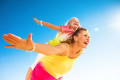 Happy trendy mother and child on seashore having fun time. Colorful and wonderfully cheerful mood. happy trendy mother and child in colorful clothes on the Royalty Free Stock Photo