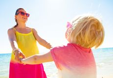 Happy trendy mother and child on seashore having fun time. Colorful and wonderfully cheerful mood. happy trendy mother and child in colorful clothes on the Stock Photos