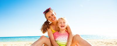 Happy trendy mother and daughter sitting on beach. Colorful and wonderfully cheerful mood. happy trendy mother and daughter in colorful clothes sitting on the Royalty Free Stock Image