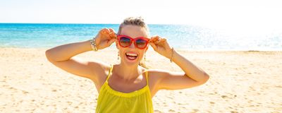 Happy modern woman on seashore holding sunglasses Royalty Free Stock Photo
