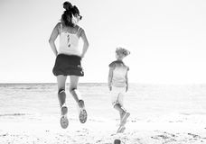 Modern mother and child in colorful clothes on beach jumping. Colorful and wonderfully cheerful mood. Seen from behind modern mother and child in colorful Royalty Free Stock Photos