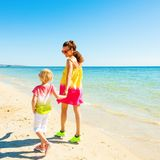 Modern mother and daughter on beach walking. Colorful and wonderfully cheerful mood. Seen from behind modern mother and daughter in colorful clothes on the beach Stock Photos